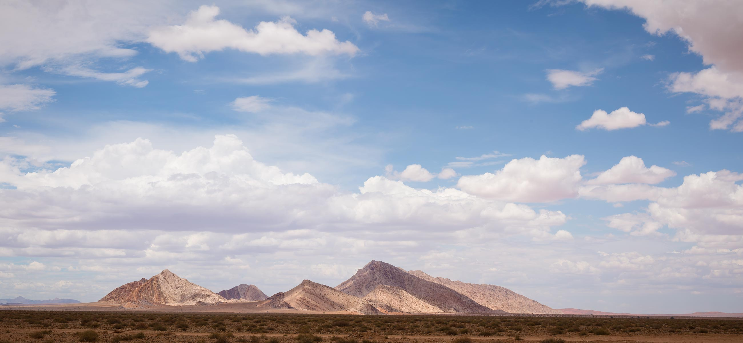 mountain rising from the flat eart desert in namibia with blue sky with clouds photo expedition