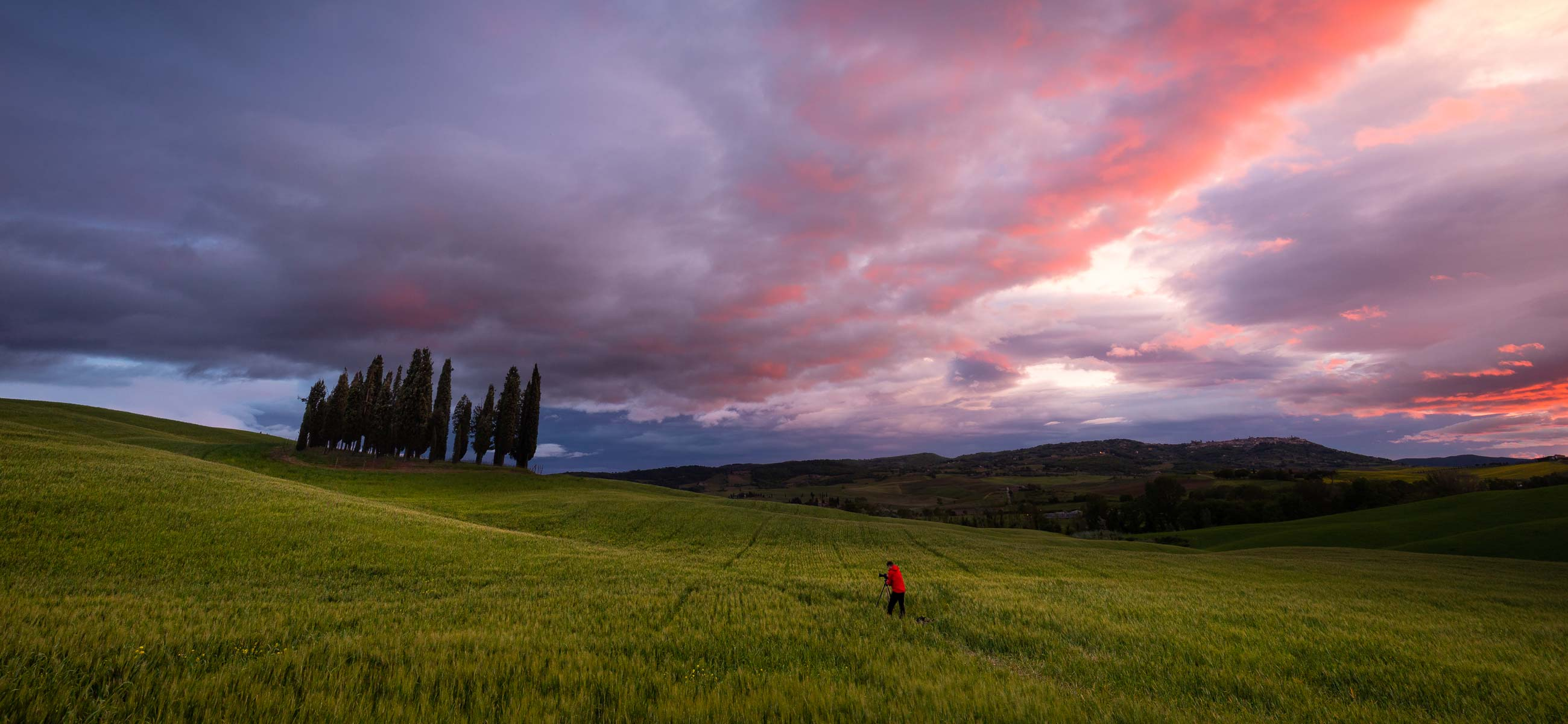 red sunset with photographer in-green-field-with-cypress-trees in Val d'Orcia during photography workshop